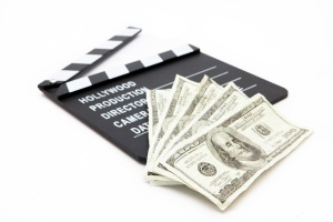 Film slate and money lying against white background